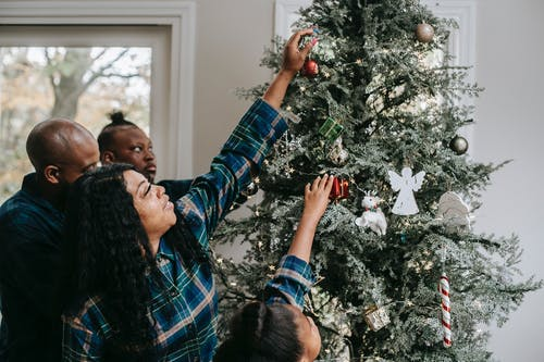 Smiling African American family wearing pajamas decorating fir tree with toys at Christmas Eve
