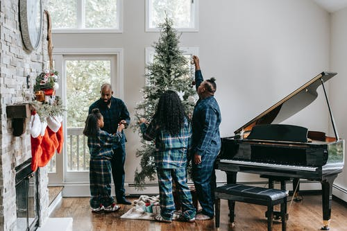 Full body of African American family putting Christmas toys on tree while spending holidays together