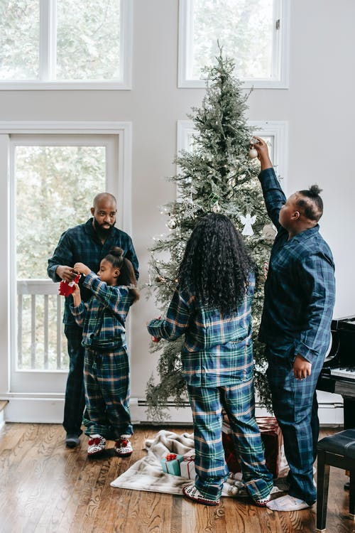 Full body of African American family decorating Christmas tree placed near window in cozy apartment