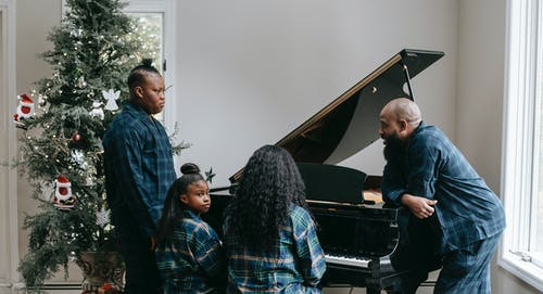 Black family playing piano together in cozy room