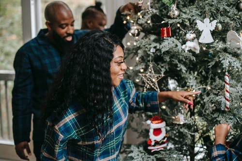 Smiling African American family decorating Christmas tree during New Year holidays in cozy home in winter day