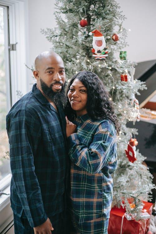 Loving black couple embracing near fir tree