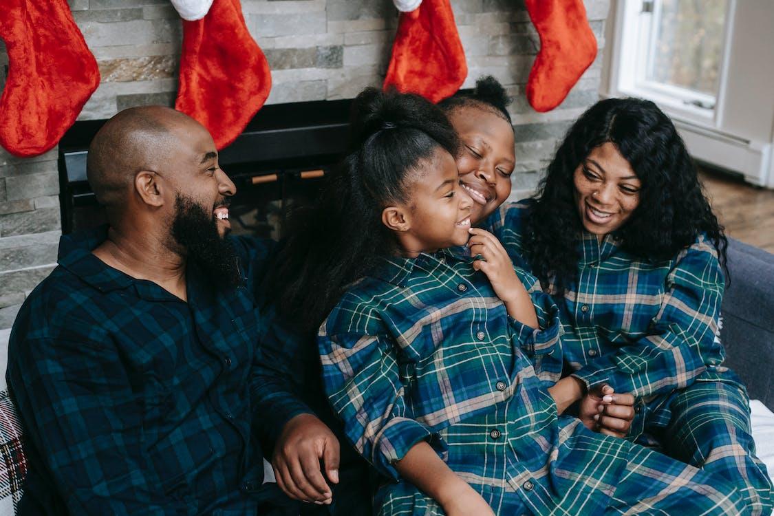 Joyful black family cuddling together on sofa