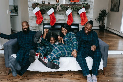 Glad black family having fun on couch