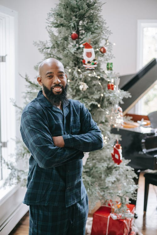 Smiling African American male wearing pajama smiling brightly while standing near spruce decorated with garlands and toys
