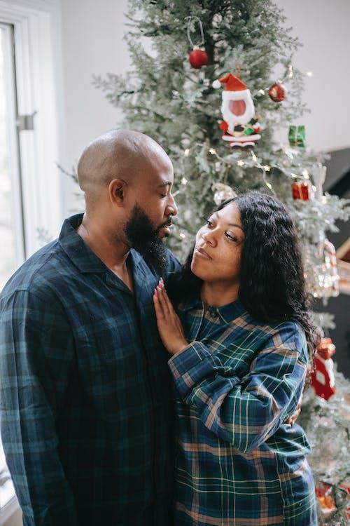 Loving black couple hugging near Christmas tree