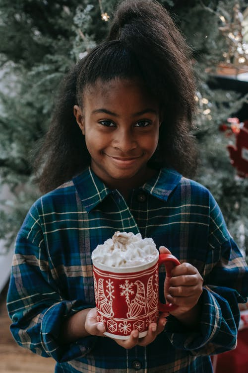 Smiling black child with hot coffee with cream