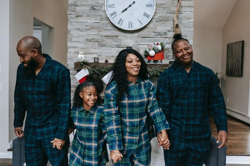 Happy African American family smiling happily while holding hands in living room with Christmas decorations