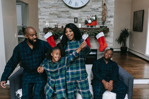 Cheerful African American family in same clothes gathering in cozy living room decorated with Christmas stockings