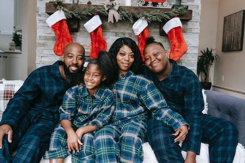 Zwarte En Gelukkige Familie In Pyjama's Op De Bank Tijdens De Kerstvakantie