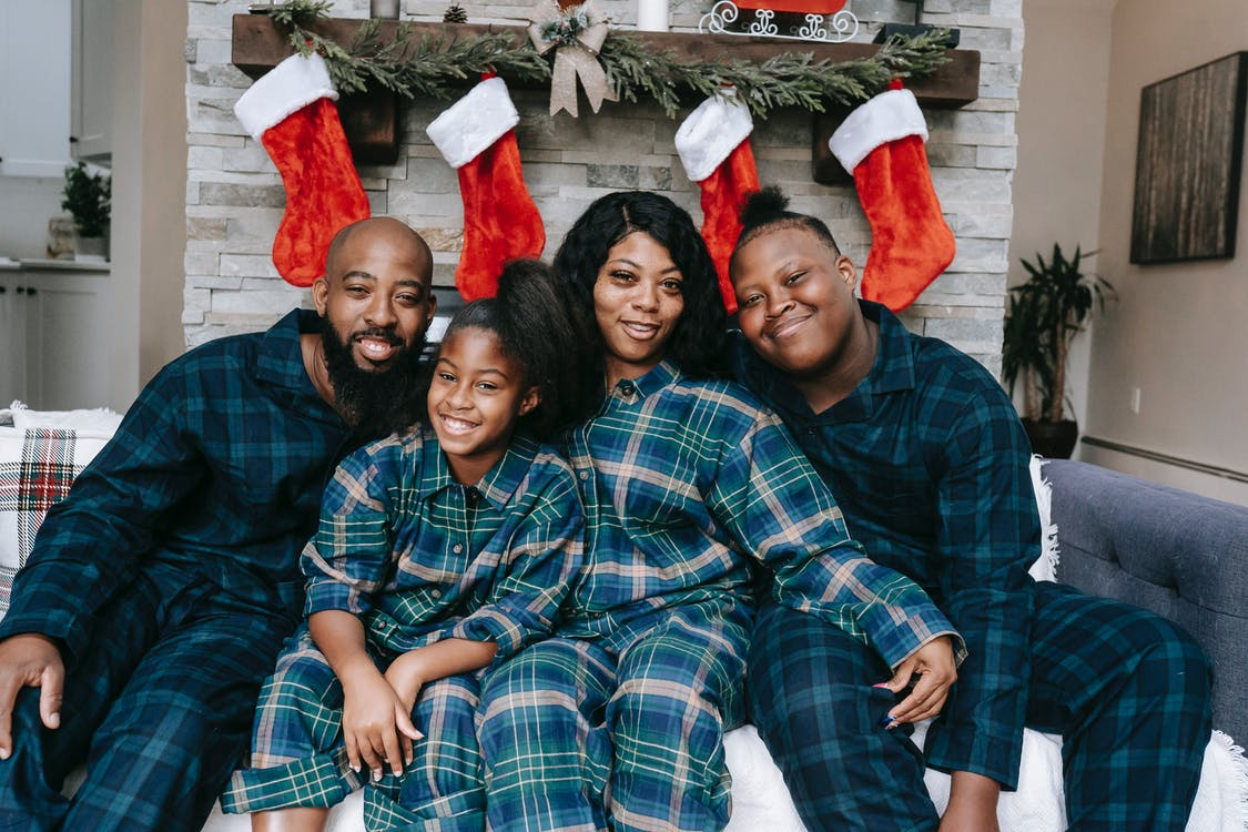 Happy black family in pajamas on couch during Christmas holidays