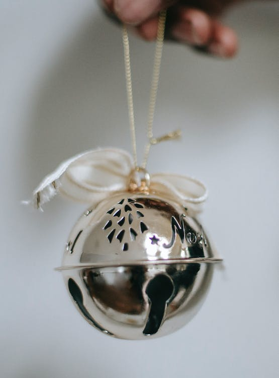 Person holding silver jingle bell with ribbon