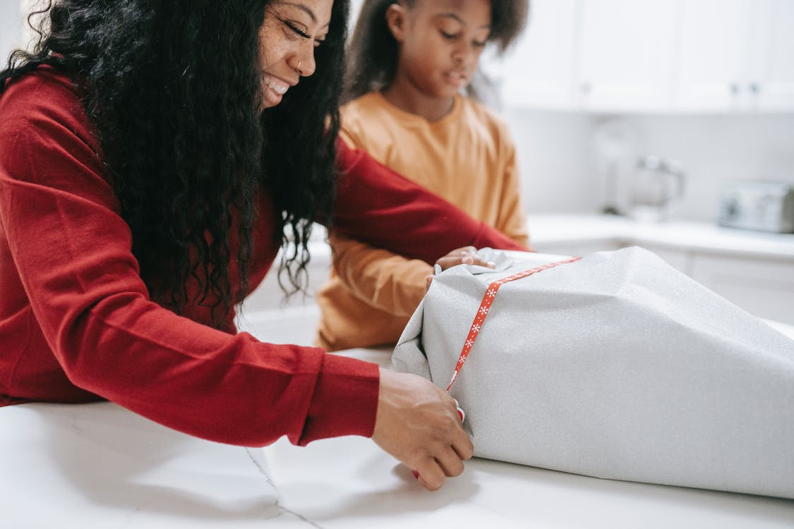 Cheerful crop black mother packing box of gift prepared for Christmas holidays with help of daughter