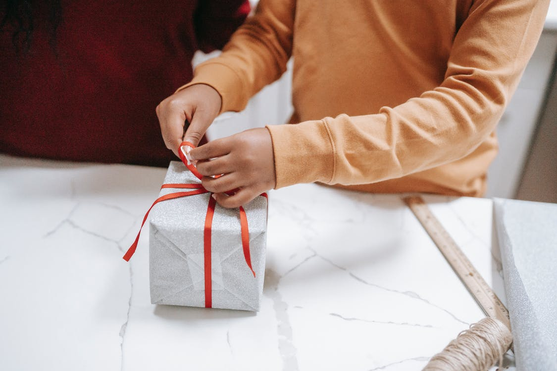 Crop ethnic child tying ribbon on gift box at home
