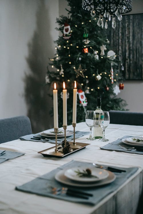 Table setting with dishware and cutlery near flaming candles and decorative fir tree at home