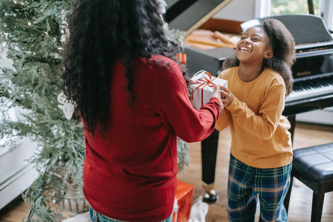 Crop anonymous black woman passing gift box to cheerful daughter during New Year holiday at home