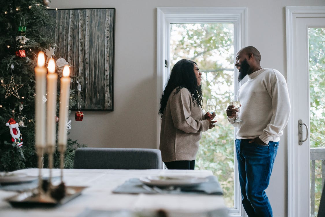 Smiling black couple with glass of champagne celebrating Christmas holiday