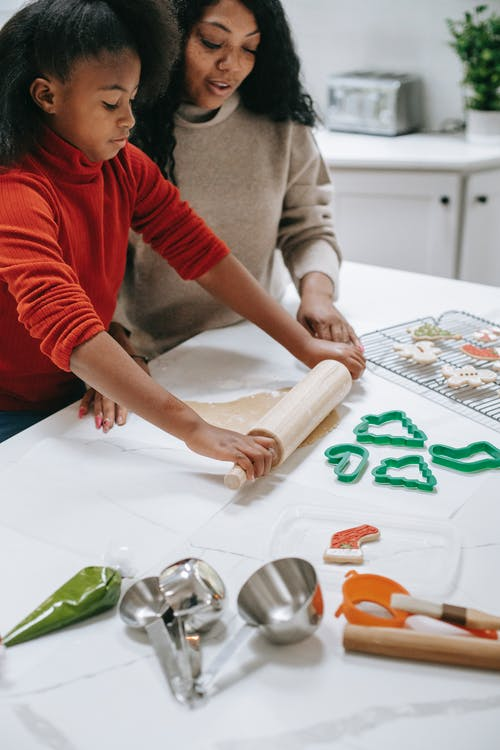 Crop focused African American child rolling out dough near parent while preparing gingerbread cookies at home