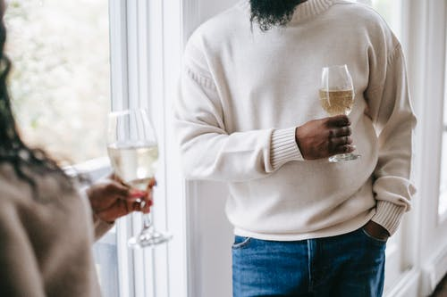 Crop black man with champagne near unrecognizable girlfriend at home
