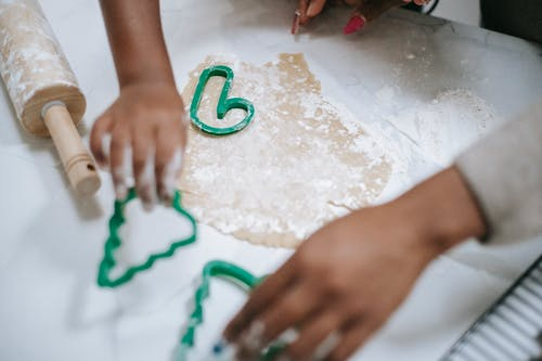 From above of crop anonymous black kid and parent using decorative pastry cutters on table with dough
