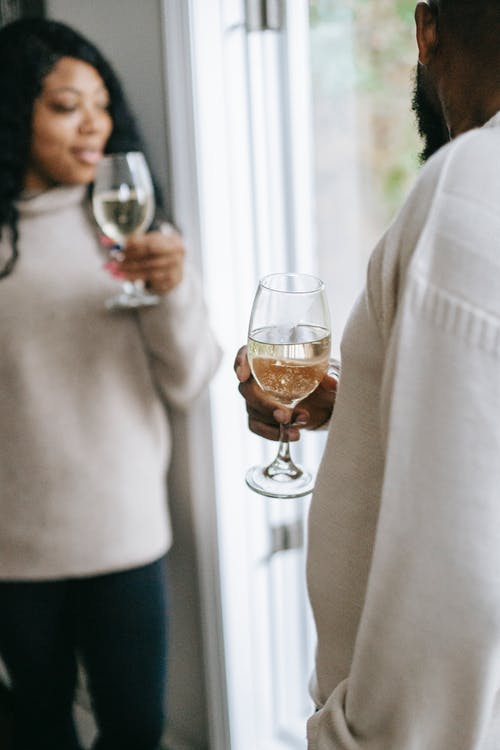 Crop black couple drinking champagne at home