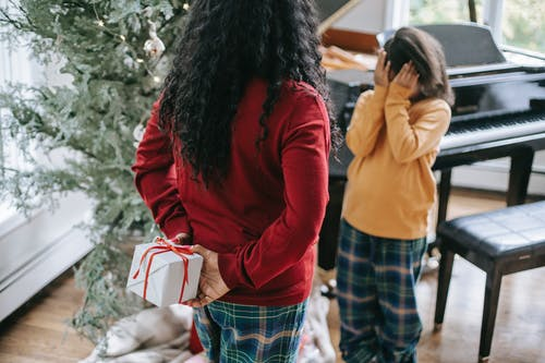 Unrecognizable black woman hiding gift box from daughter