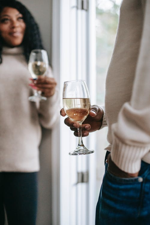 Crop black woman interacting with anonymous partner with champagne