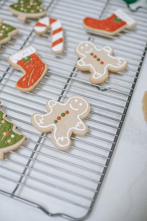 From above of assorted gingerbread cookies in form of snowman and sock with creative ornament for New Year holiday