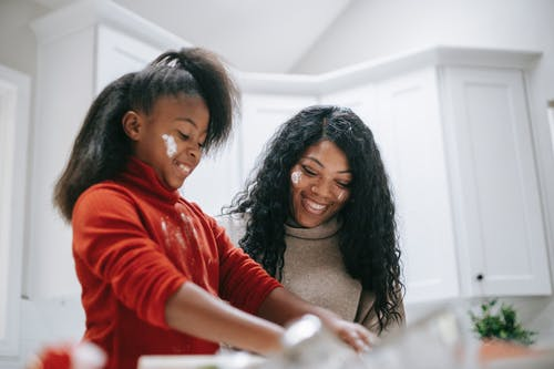 Cheerful messy African American child with flour on face cooking with parent at home
