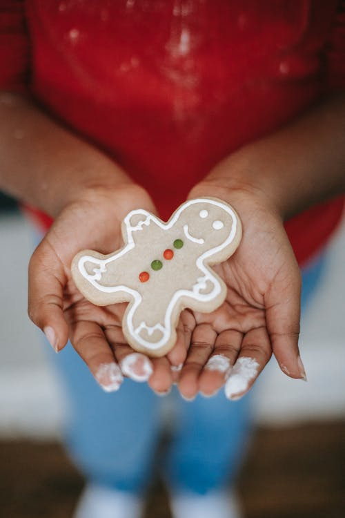 Crop black child showing gingerbread cookie during Christmas holiday