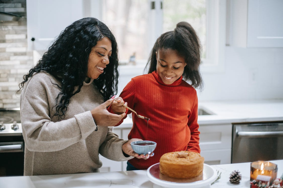 Young content black woman with girl decorating yummy sponge cake with chocolate glaze during New Year holiday