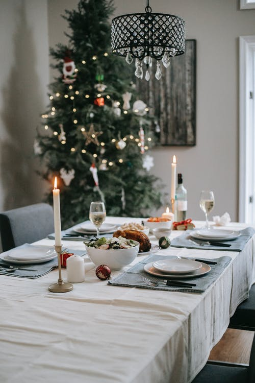 Table setting with burning candles and yummy dishes near fir tree with shiny garland during New Year holiday in house