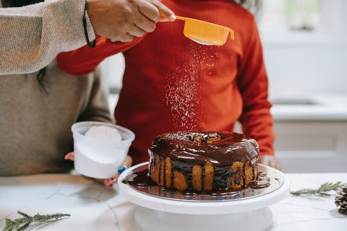 Crop ethnic parent with child decorating cake with icing sugar