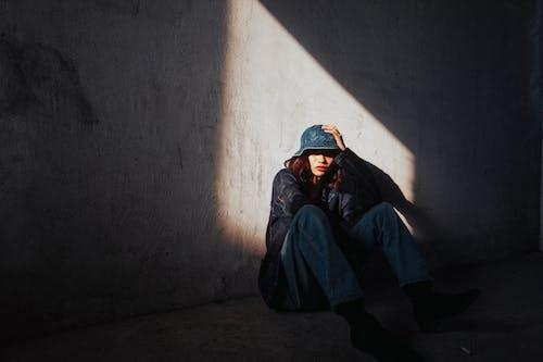 藍色連帽衫和藍色針織帽坐在地板上的男人