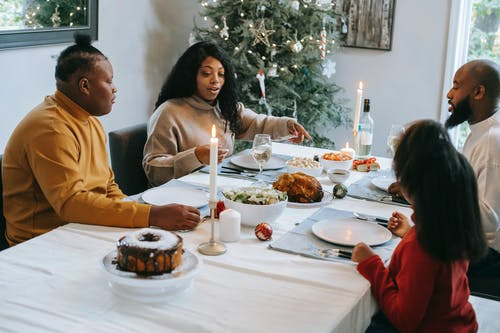 Black family dining at served table during Christmas holiday