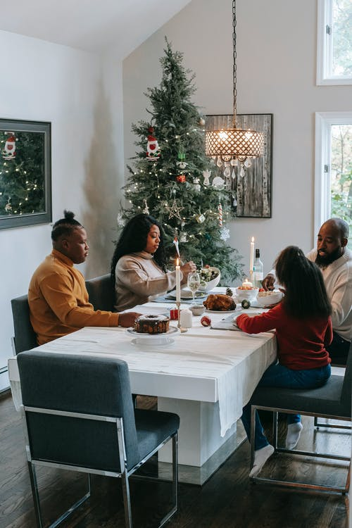 African American parents with anonymous daughter and son dining at table near shiny fir tree in house