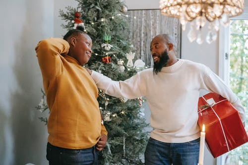 Happy bearded African American man with red box touching shoulder of cheerful black son with hand behind head during Christmas holiday while looking at each other