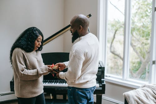 Side view of surprised African American woman receiving present from beaded husband during holiday celebration in room with piano near window