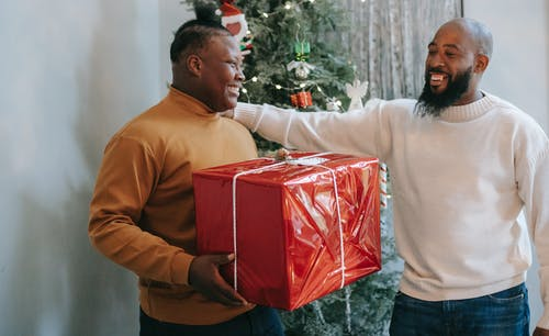 Smiling black father hugging son while presenting box