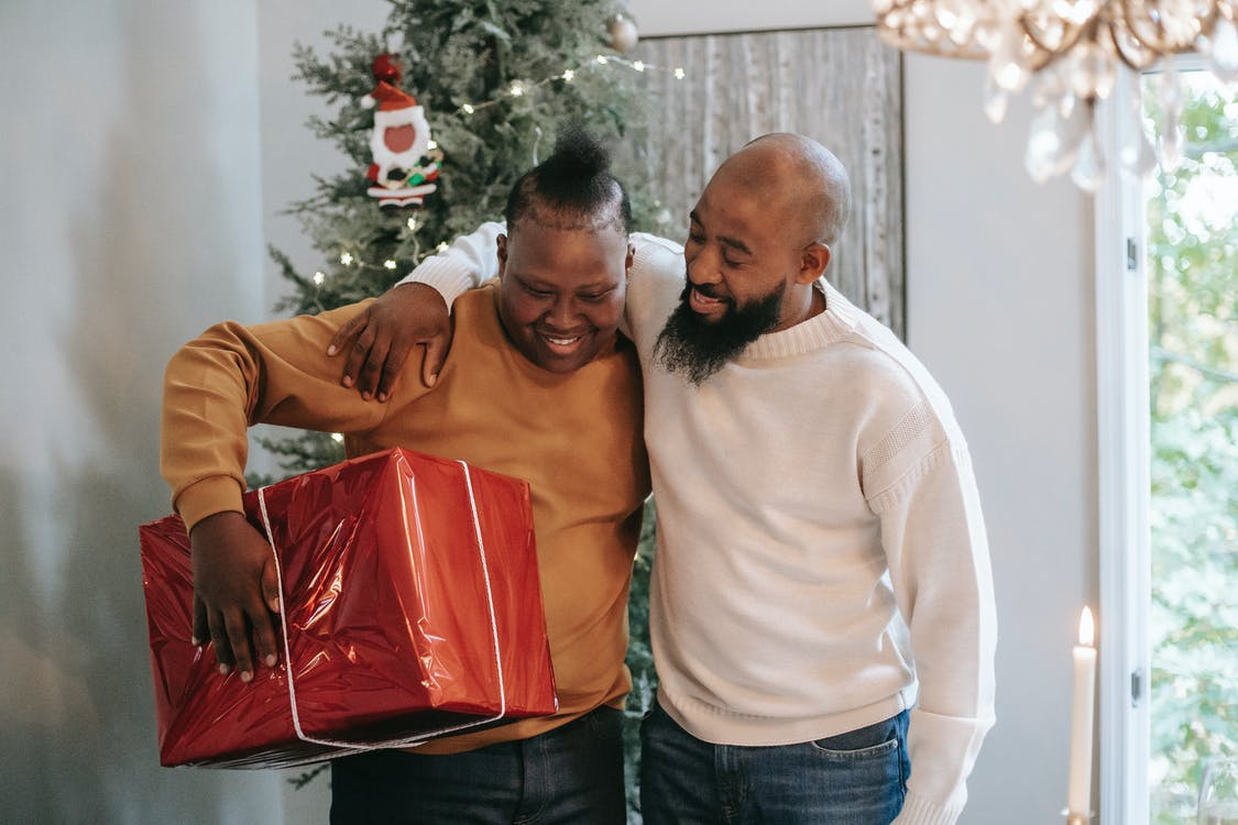 Cheerful black father hugging son