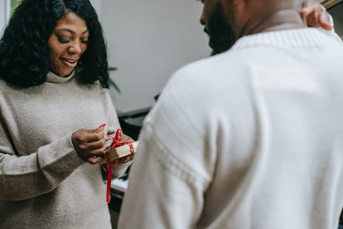 Black couple in sweaters congratulating each other on Christmas
