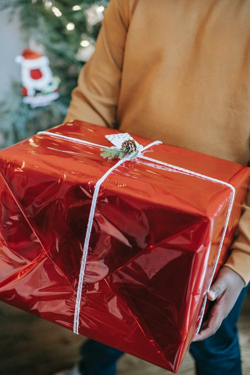 Crop anonymous African American male demonstrating Christmas present in bright glimmering package on blurred background of decorations
