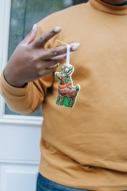 Black man showing bright figure of Christmas reindeer