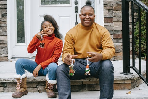 Happy black teenagers with handmade Christmas decorations