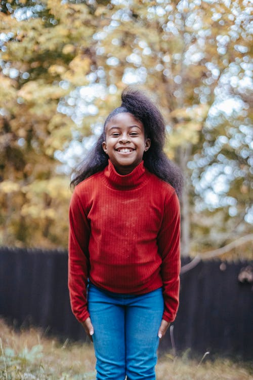 Black funny happy girl in warm clothes smiling at camera