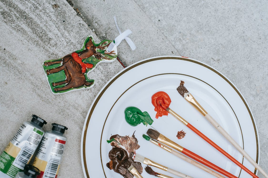 Flat lay of Christmas deer near tubes placed near plate with brushes and mixture of colorful paints