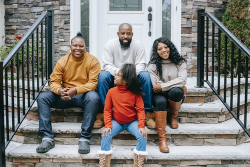 Happy black family sitting on stairs of modern house