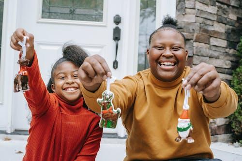 Cheerful smiling black teens demonstrating Christmas decorations