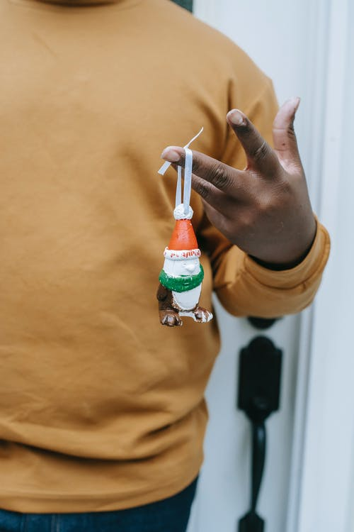 Crop anonymous African American male demonstrating handmade present hanging on ribbon on hand