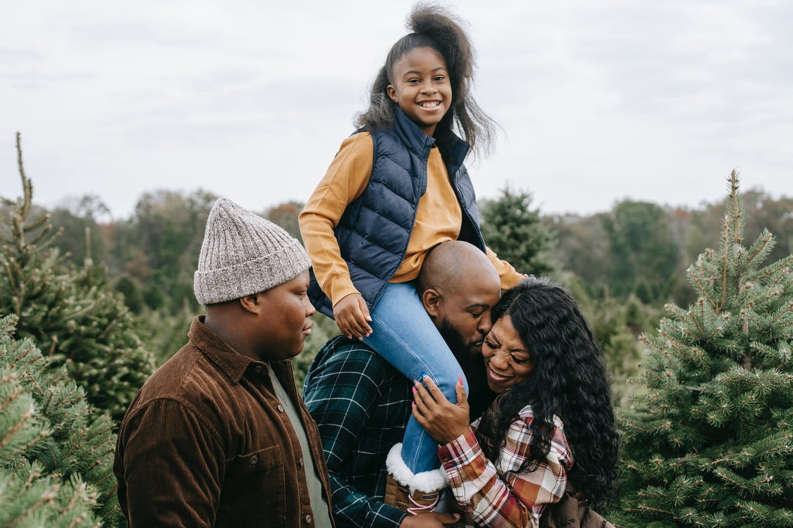 Happy African American family hugging and kissing in green lush spruce under cloudy gloomy sky